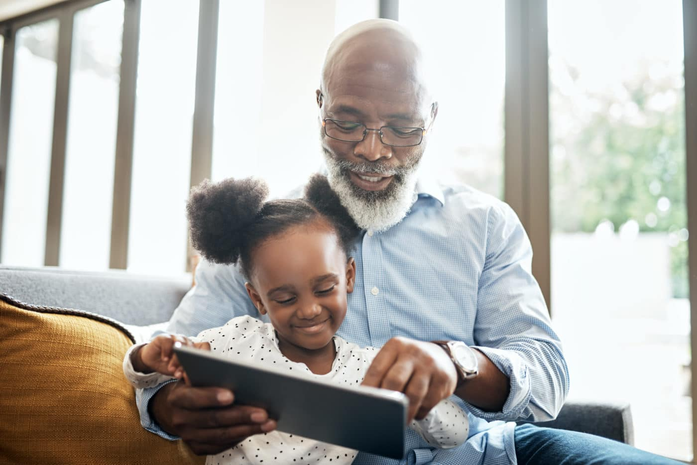 Shot of a little girl using a digital tablet with her grandfather at home