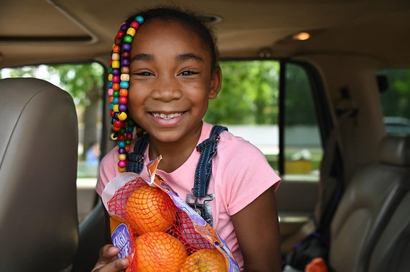 JaLisa's face lit up when she saw a bag of oranges loaded into her grandma's car at a Care and Share Food Bank's Mobile Food Pantry.