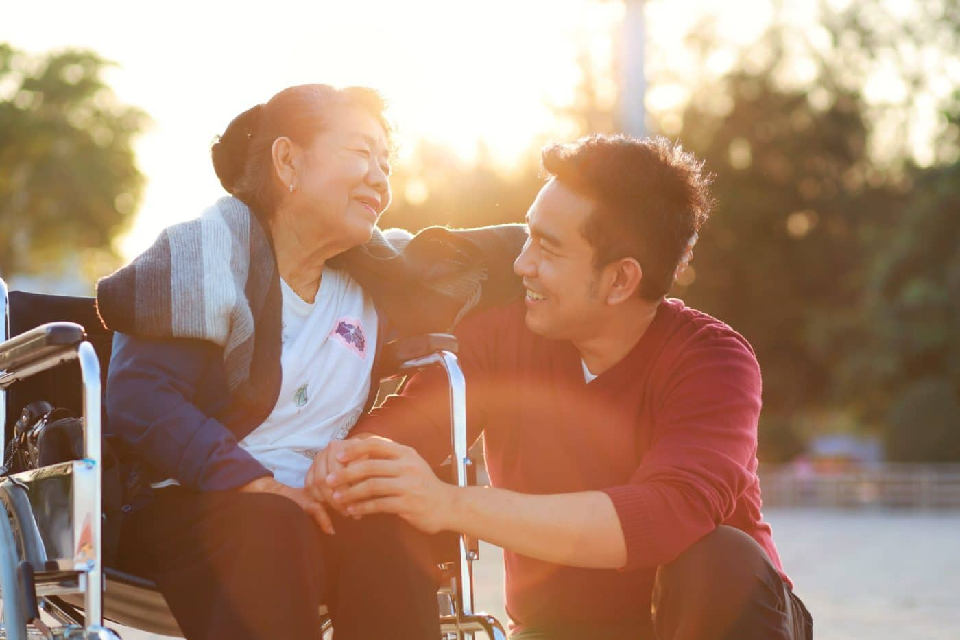 Couple Sitting On The Park At Sunset Time