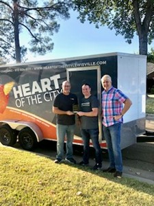 Three men accepting award for Heart of the City